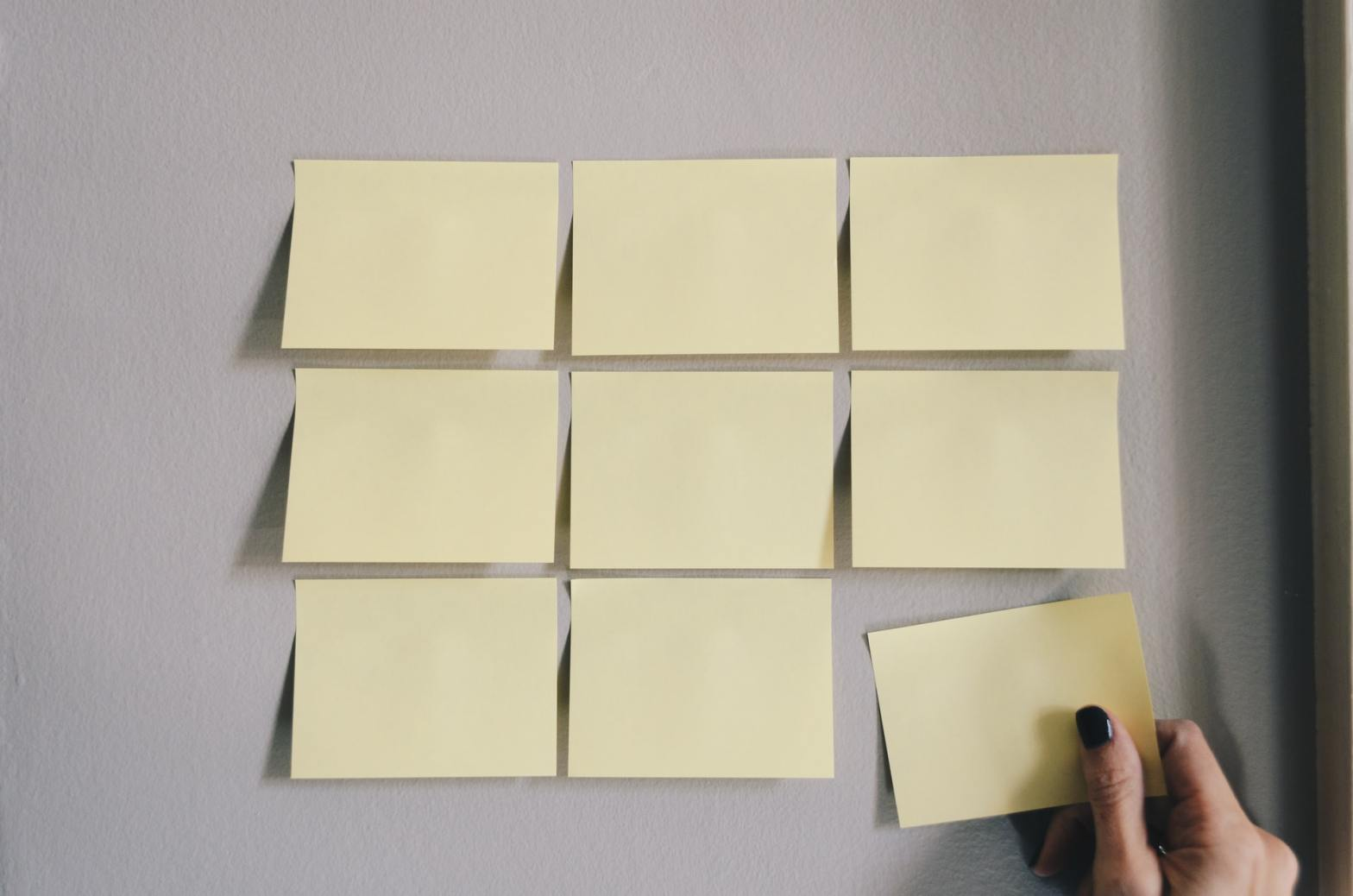A hand placing post-it notes in a 3x3 arrangement. Photo by Kelly Sikkema on Unsplash